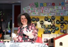 A profile picture of teacher and leader Jane Doyle, getting her hands dirty at a student desk.